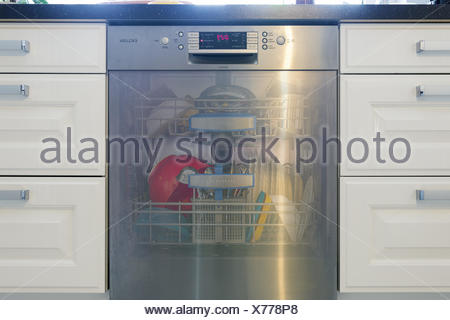 dishwasher filled with transparent flap - Stock Photo