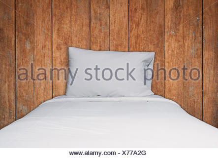 Close up white bedding and pillow on wooden texture background - Stock Photo