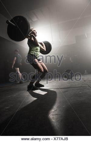 Mid adult woman lifting barbell - Stock Photo