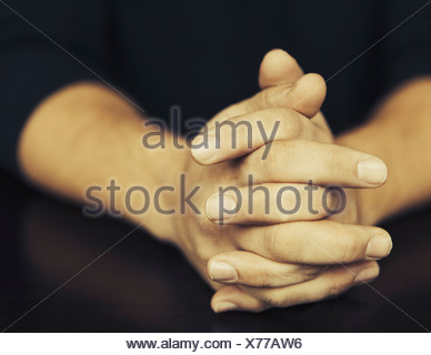 The clasped hands of a man wearing dark coloured clothes - Stock Photo