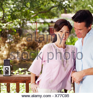 Mature couple leaning against a railing - Stock Photo