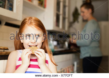 Girl eating biscuit in kitchen - Stock Photo