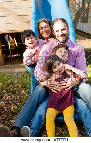 Family in a row between each others legs on playground slide, looking at camera smiling - Stock Photo