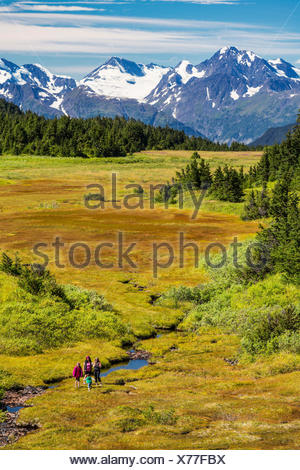 A small group of women hiking along a stream in Turnagain Pass, with patches of snow on the Chugach Mountains in the background - Stock Photo