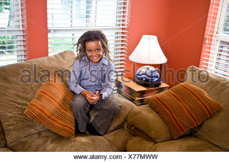 Mixed race boy sitting on sofa on living room - Stock Photo