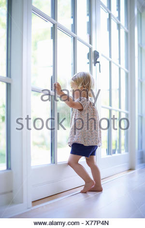 Portrait female toddler looking out of patio doors - Stock Photo