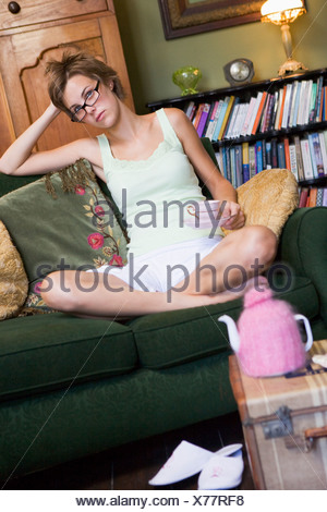 Young woman sitting on sofa at home drinking tea - Stock Photo