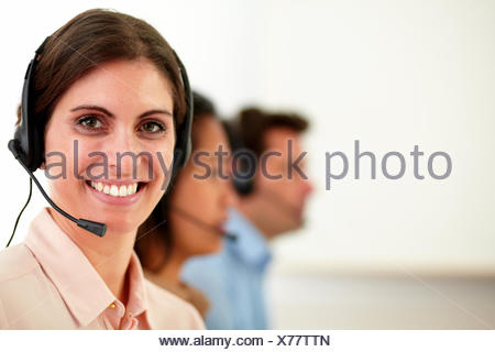 Portrait of lovely operator lady with microphone smiling at you while sitting beside her coworker on workplace - copyspace. - Stock Photo