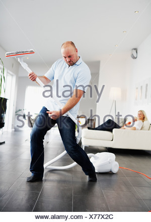 A man pretending the vacuum cleaner to be a guitar Sweden. - Stock Photo