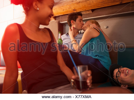 Young couple kissing, friends sitting nearby - Stock Photo