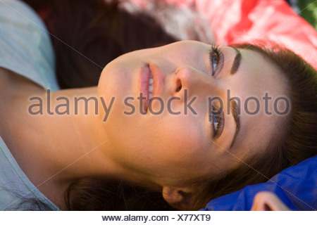 Woman lying on sleeping bag daydreaming side view close up - Stock Photo