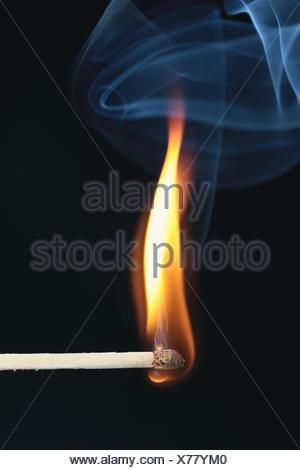 ignited match with blue smoke on black background - Stock Photo