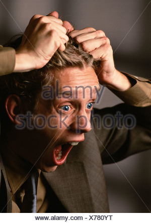 Man with mouth and eyes wide open, pulling hair, close-up - Stock Photo