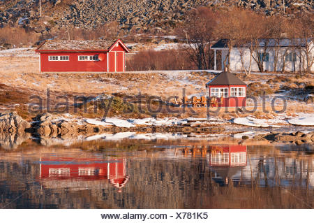 Some rorbuer reflected on the water of the near fiord in the Lofoten Islands, Norway. - Stock Photo