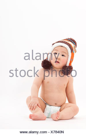 Baby boy wearing knit hat and looking away, - Stock Photo
