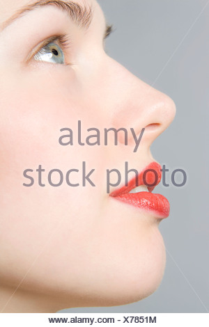 Close-up of young woman's face, profile, red lips - Stock Photo