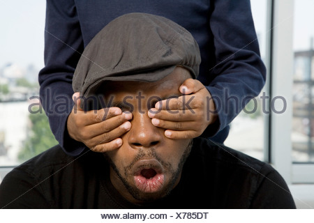 A boy's hands covering his father's eyes - Stock Photo