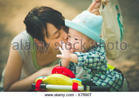 Mother kissing her son while on his toy tricycle - Stock Photo