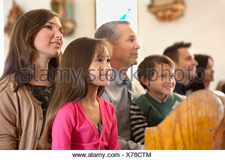Family sitting together in church - Stock Photo