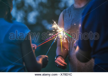 Cropped shot of women and girl igniting sparklers together at dusk on independence day, USA - Stock Photo