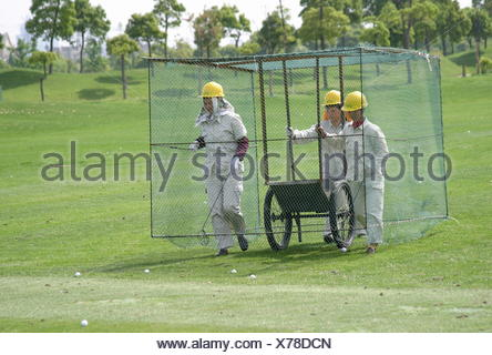 Women in a cage walk over the driving range to collect golf balls, Tomson Golf Club, BMW Asian Open 2004, Shanghai, China - Stock Photo