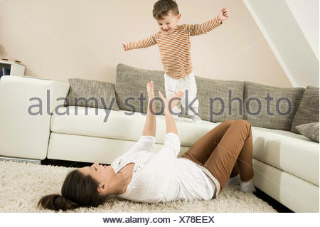 Mother and son are romping in living room, smiling - Stock Photo