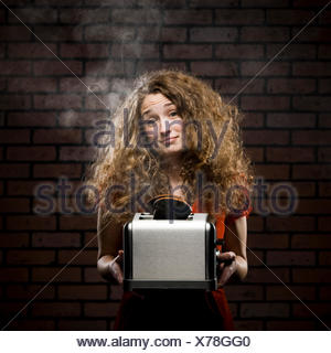 woman holding a smoking toaster with her hair all messed up - Stock Photo