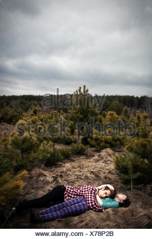 Teenage couple lying in a meadow embracing - Stock Photo
