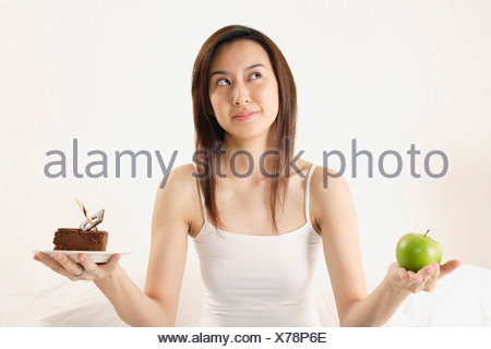 Woman deciding on piece of cake or apple - Stock Photo