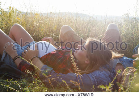 Young pregnant couple lying in field - Stock Photo