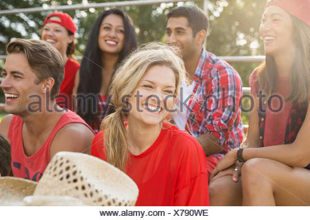 Friends laughing at sporting event - Stock Photo