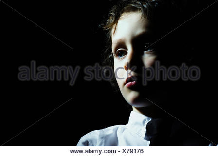 A young boy looking away in contemplation - Stock Photo