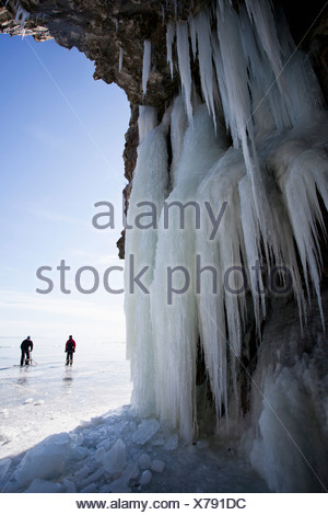 View of icicles with people hiking in background - Stock Photo