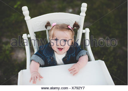Portrait of baby girl in high chair - Stock Photo