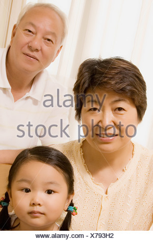 Portrait of a mature couple with their granddaughter - Stock Photo