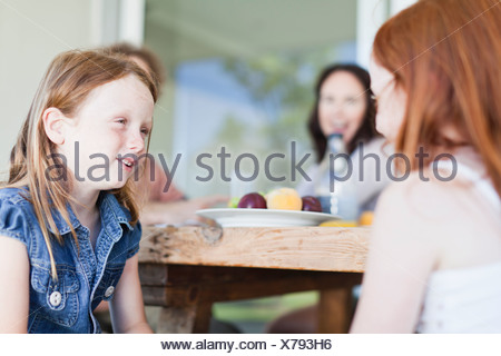 Girls talking at breakfast table - Stock Photo