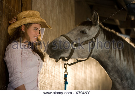 Young woman with white Gelding horse in stable - Stock Photo