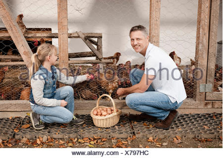 Father and daughter at henhouse on organic farm - Stock Photo