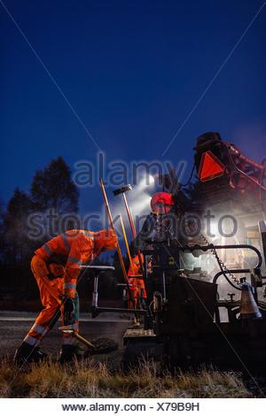 Sweden, Narke, Two manual workers repairing road at night - Stock Photo