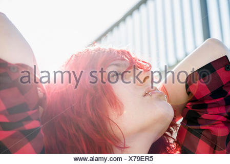 Teenage girl portrait day-dreaming red dyed hair - Stock Photo