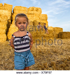 Three children playing on field of hay bales - Stock Photo