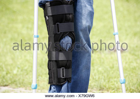 Person, detail, feet, knees, injury, crutches, rail, knee injury, trousers, jeans, bandage, knee prop, bone prop, black, accident, impediment, unwieldy, danger, insurance, encroachment, walking impediment, healing, accessory, person, - Stock Photo