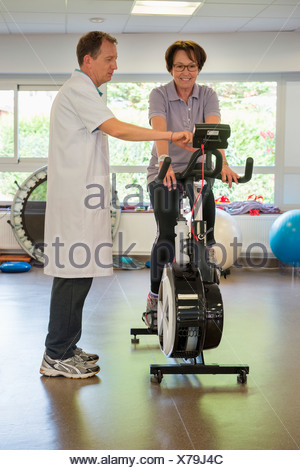 Physical therapist helping a patient to ride an exercise bike - Stock Photo