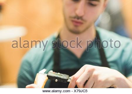 Young man wearing apron crafting wood object with tool, looking down - Stock Photo