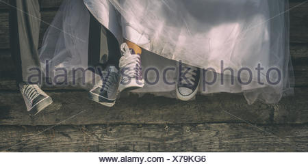 Low-section of newlyweds in canvas shoes - Stock Photo