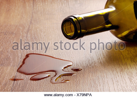 Wine glass and spilled red wine on a durable vinyl flooring with wood effect - Stock Photo