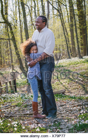 Young girl and father hugging in woods - Stock Photo