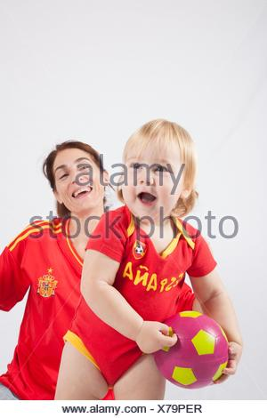 smiling blonde baby sixteen month old and mother with red shirt of Spanish soccer team. - Stock Photo