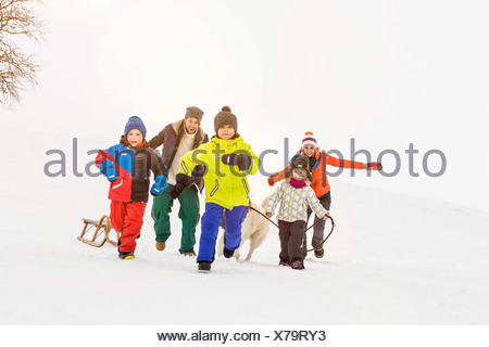 Family with three children running in snow - Stock Photo