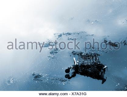 Abandoned shopping trolley submerged in water. - Stock Photo